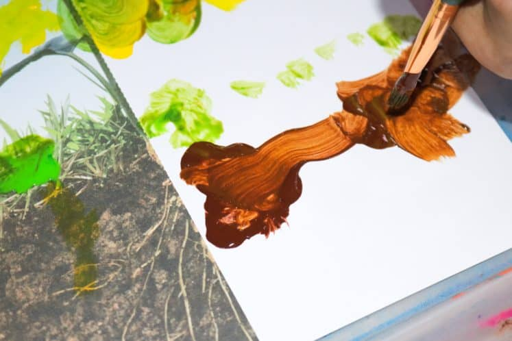 preschooler painting sunflower roots on cardstock