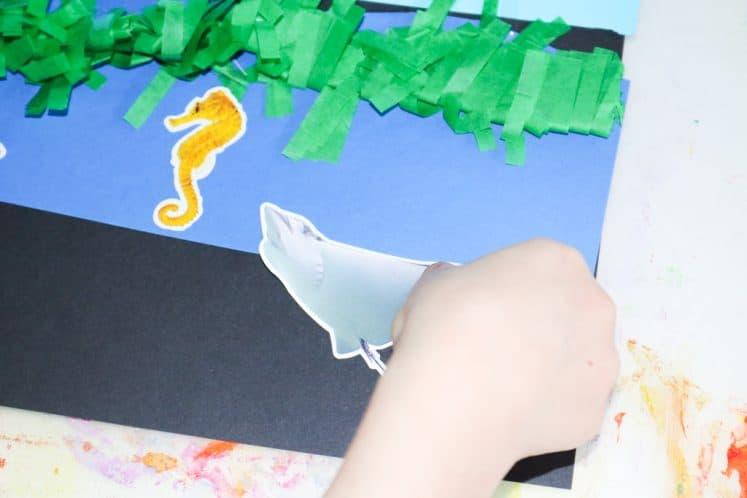 child placing sea creature sticker on ocean zones collage