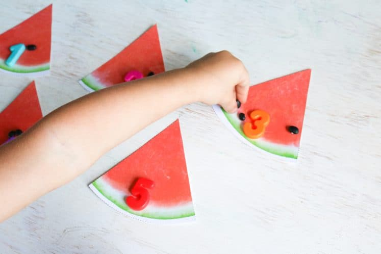preschoolers counting beans on paper watermelon slices