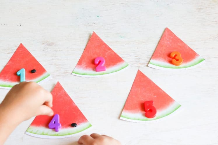 preschooler putting black beans on paper watermelon slices