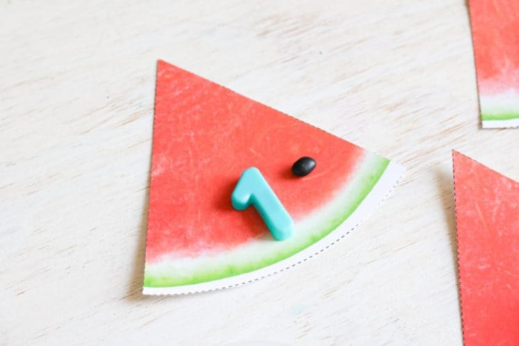 watermelon slice with magnetic number one and a black bean on it