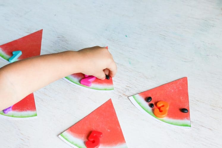 preschooler using paper watermelon slices as counting mats