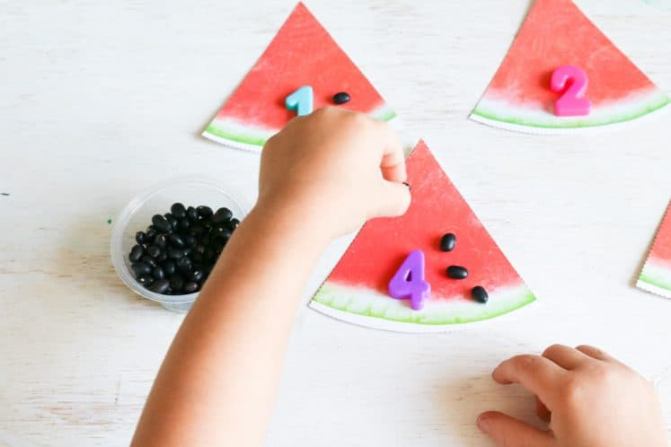 preschooler counting black beans on paper watermelon slice