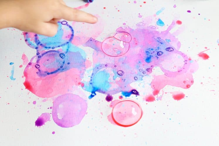 preschooler popping colored bubbles on paper
