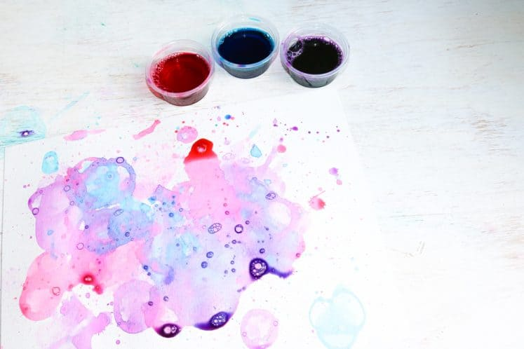 bubble painting for kids and 3 small plastic cups filled with colored bubble solution