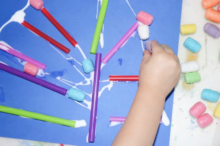 child using straws and cornstarch noodles and straw pieces