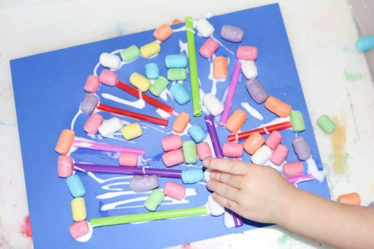 child making coral collage using cornstarch noodles and straw pieces on blue cardstock