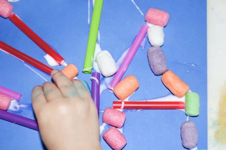 child placing cornstarch noodle onto coral collage process art