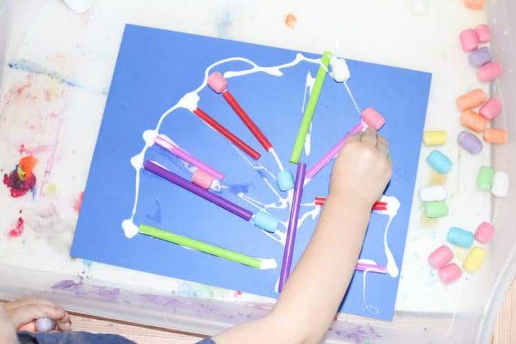 child pressing cornstarch noodles onto coral collage process art