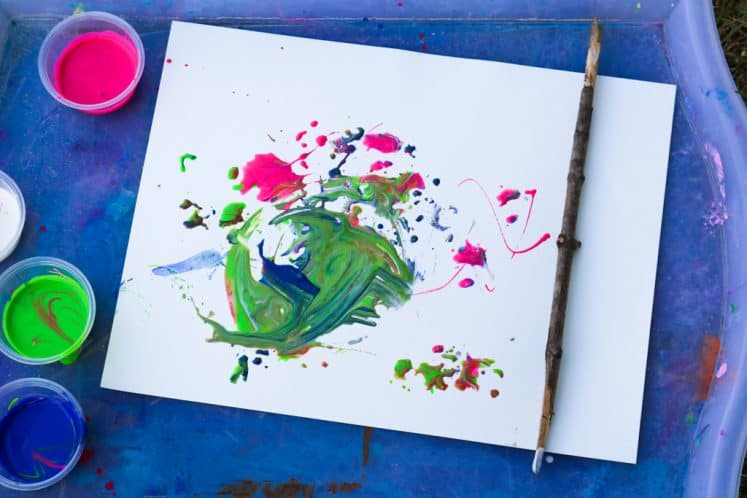 child's tree painting on tray next to stick