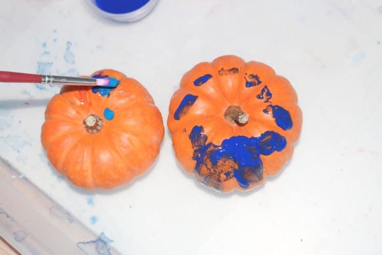 preschooler painting mini pumpkin