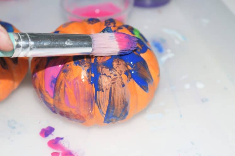 child using paintbrush to paint mini pumpkin