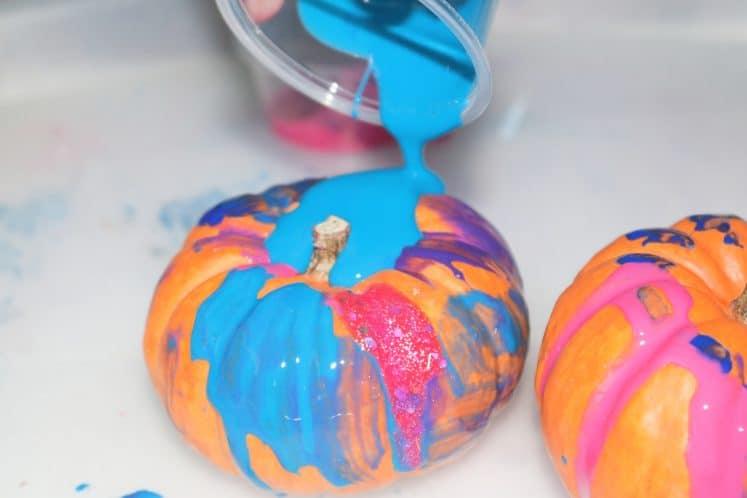 child pouring paint over mini pumpkin