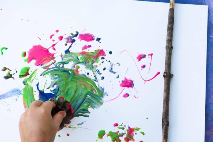 preschooler making tree art using paint and pinecone