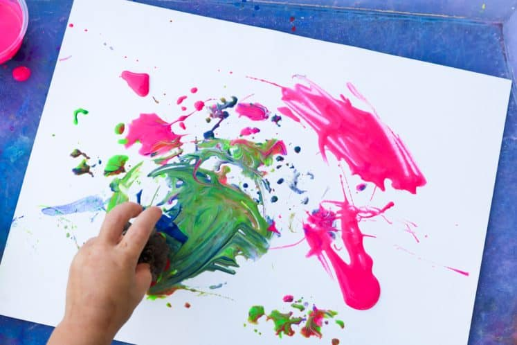 child using pinecone and paint to stamp on cardstock