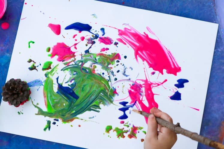 preschooler using stick as a paintbrush while making tree painting for kids