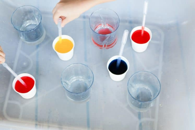 children exploring color mixing with water and eyedroppers