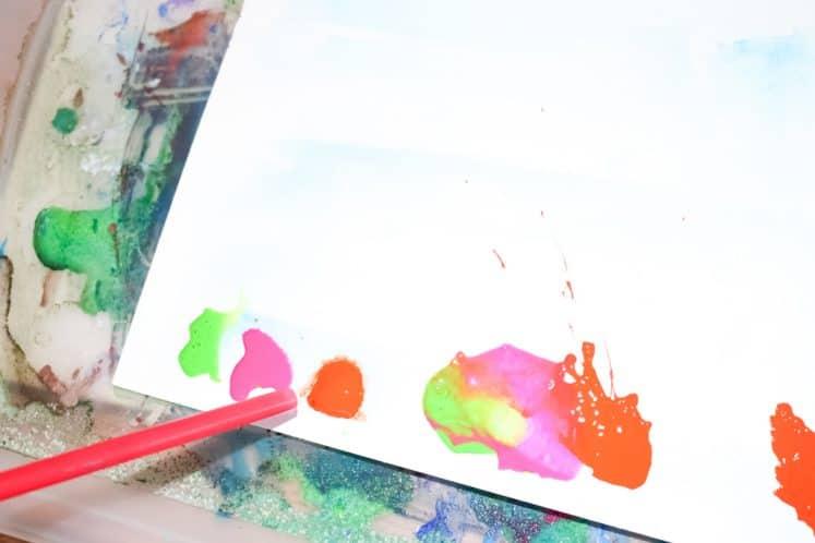 child using straw to make blow painting process art