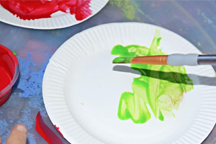 preschooler painting paper plate green while making apple craft
