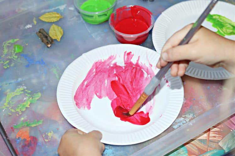 preschool painting paper plate with red paint for apple craft