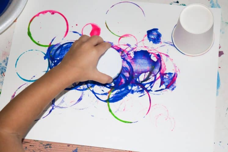preschooler using circle tools to stamp with paint