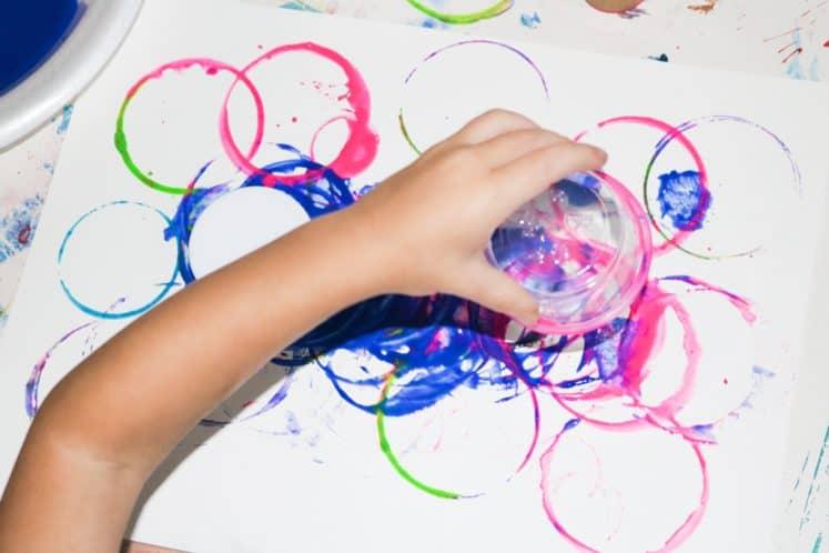 preschooler stamping with plastic cup