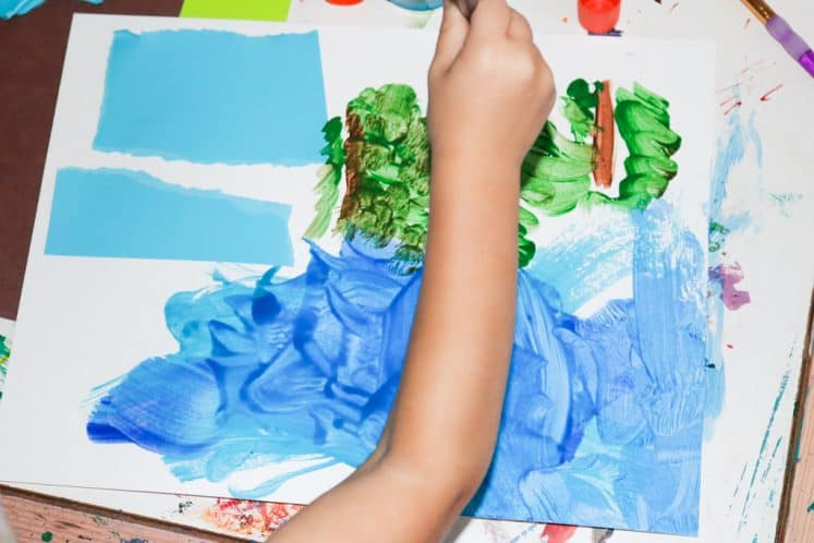child painting trees on cardstock