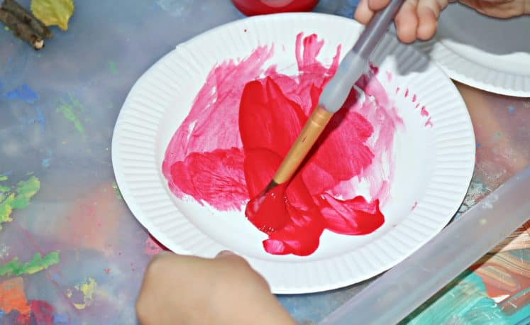 preschooler painting paper plate red while making apple craft
