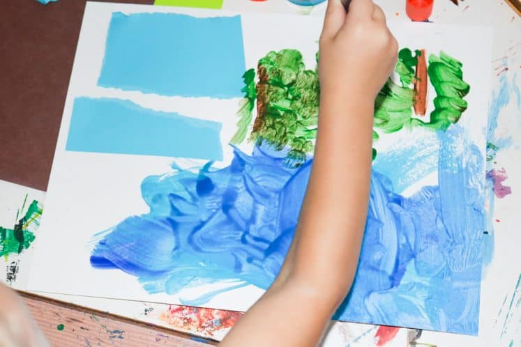 child working on river painting process art