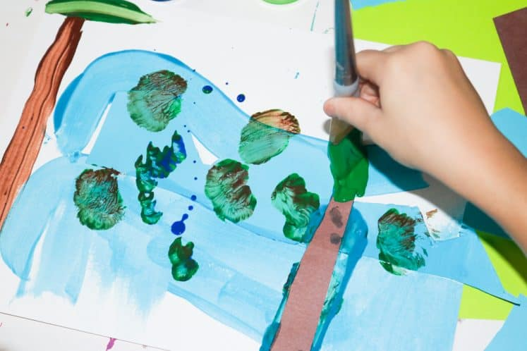child painting leaves on tree near river