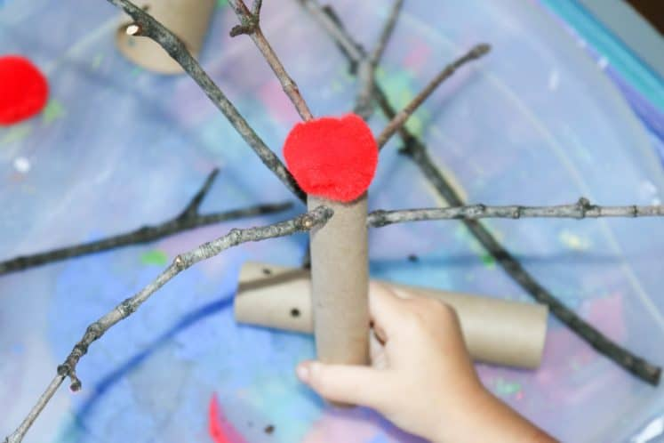 preschooler holding pretend apple tree made from sticks, cardboard tube, and red pompom