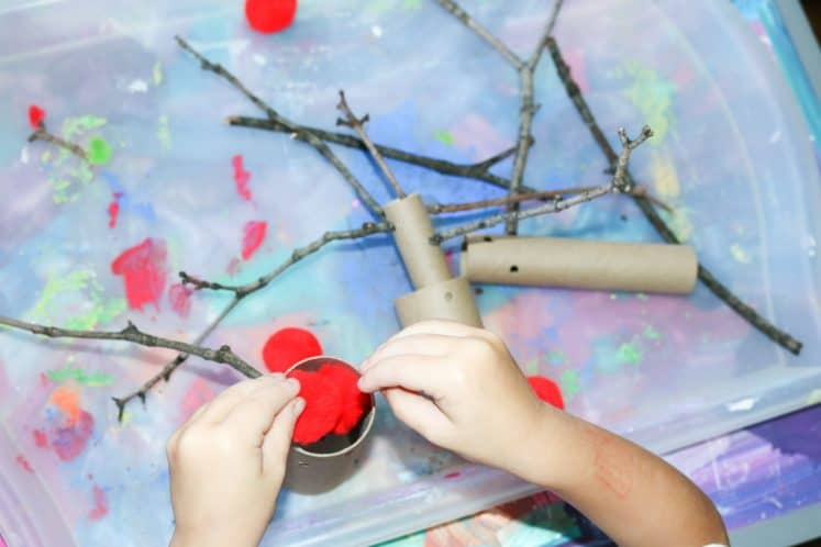 preschooler putting red pompoms into cardboard tube