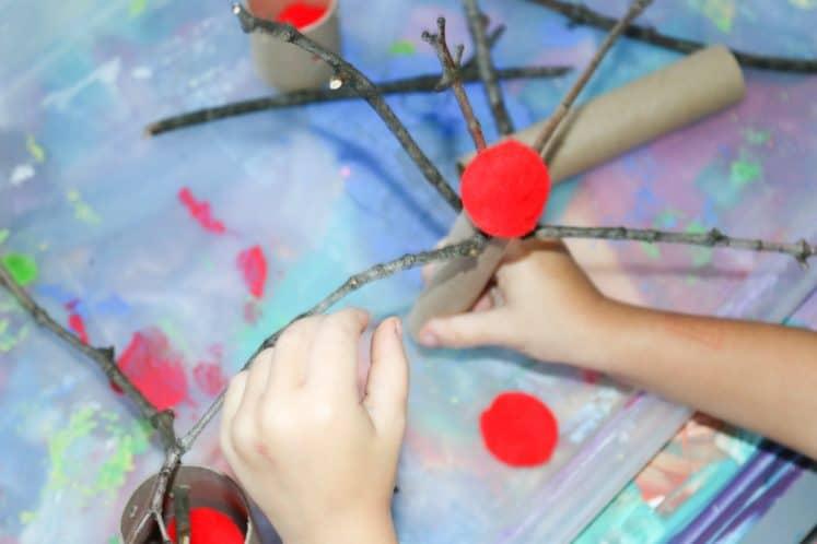 preschooler pushing sticks into cardboard tube to make pretend apple tree