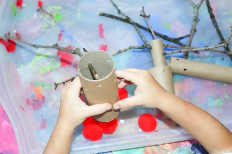 preschooler holding cardboard tube over tray