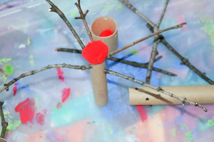 pretend apple tree made from red pompoms, sticks, and cardboard tubes on tray