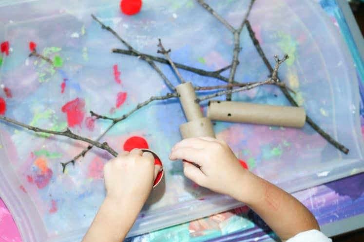 preschooler filling cardboard tube with red pompoms